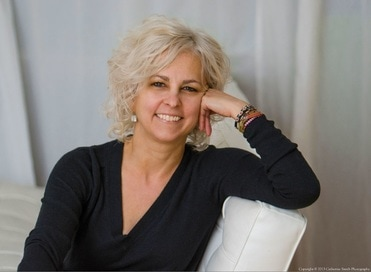 Kate DiCamillo sitting on a white couch